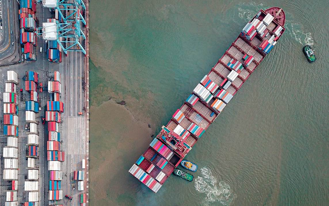 Birds-eye view of a container ship docking.