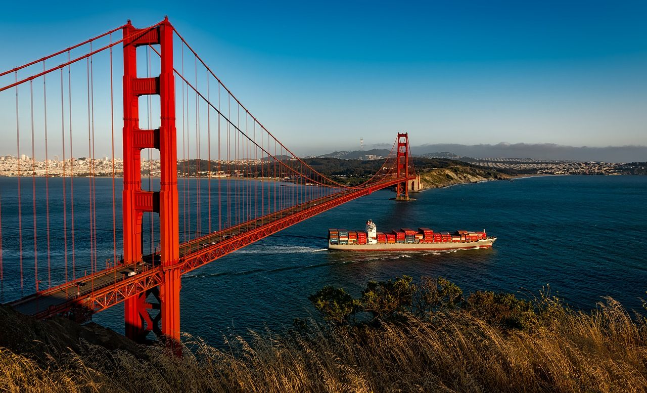 A container ship sailing out to sea under the Golden Gate Bridge.